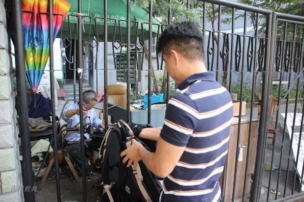 今年55岁的戴金炉大伯的修鞋摊,就摆在杭州城西文一路和古翠路的交叉口,靠东南角的翠苑四区一个封闭的铁栏门里面