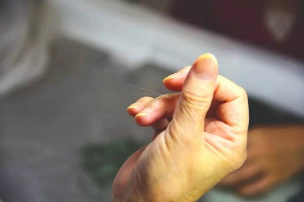 1982年,日本静冈县有一场刺绣表演,绣架前,一位手绣大师将一根细丝绒一劈再劈,劈出100多缕,穿过针眼的一缕丝线几乎肉眼难见
