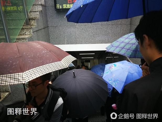 一大早住在城西的上班族急忙忙赶地铁。在杭州地铁二号线古翠路起点站出入口,撑雨伞的乘客把整个进口堵塞了。颜色图案各异的雨伞成了一道风景