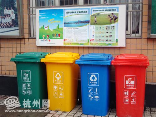 学校的大门口,四色分类垃圾桶摆在了鲜艳的位置.图片
