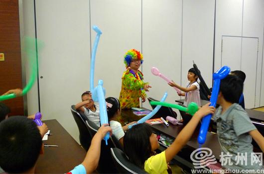 杭州网讯 做好了吗?做好了!台上台下的一唱一和,让2010杭州网义工分会外来务工者子女夏令营的课堂气氛活跃到了极点。   看看台上的老师,或许你会吓一跳这是一个小丑打扮的大男生,是什么让这个小丑那么受孩子们的欢迎呢?   不知您听说过魔法气球没有,这位小丑可是杭州城里数一数二的魔法气球高手,长条形的气球在他手里能变成各式各样的动物、植物,还有酷酷的蜘蛛侠、够潮的粉红豹,难怪台下的小候鸟们都把他当作了夏令营里最崇拜的偶像。   这堂课是杭州图书馆特地为这些小候鸟安排的,上课的这位
