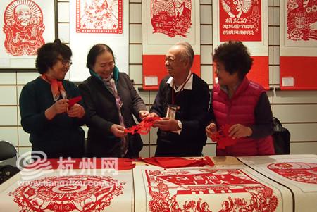 王维昌老人(右二)和他的学员们一起剪纸.高清图片